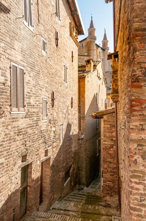The renaissance town of Urbino, Marche, Italy. A view of the Ducale Palace (Palazzo Ducale) seen from a narrow street in Urbino city, Marche, Italy