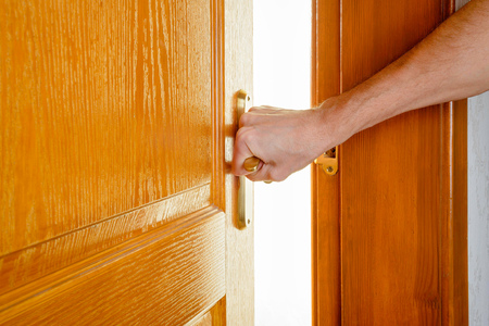 A man is opening a wooden door with a metallic handle to get out of a room and enter in an illuminated one.