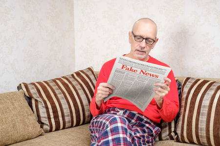 A man wearing glasses and pajamas is sitting on a couch at home, reading a newspaper reporting fake news Stock Photo