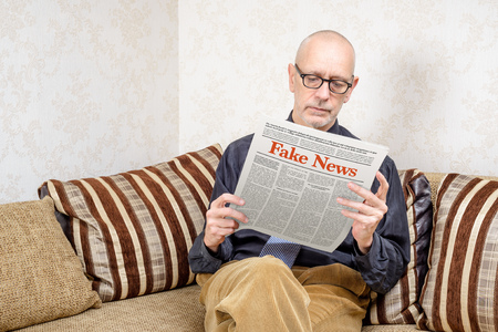 A man wearing glasses is sitting on a couch at home, reading a newspaper reporting fake news