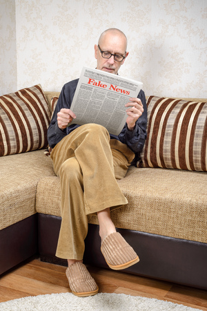 A man wearing glasses is sitting on a couch at home, reading a newspaper reporting fake news. Fake Lorem ipsum text. Stock Photo