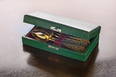 An antique golden spoons case on a wooden table. 版權商用圖片