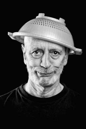 Dramatic black and white Portrait of a mad man with a plastic strainer on the head Stock Photo