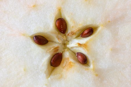 Macro of a cut apple, showing the seeds in a delicate five pointed star motive Фото со стока