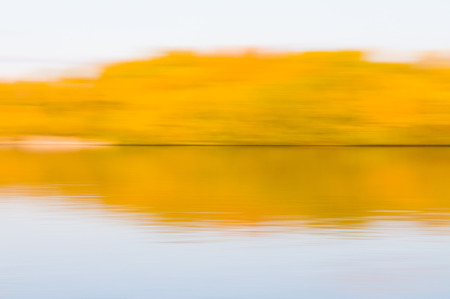 Sky and trees reflecting in the calm water of the Dnieper river in Kiev, Ukraine, with motion blur effect Stock Photo