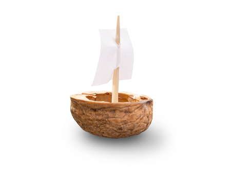 A toy made with a walnut shell with a sail, isolated on white background Banco de Imagens