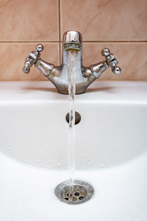 Vertical image of a tap with water flowing strongly under high pressure