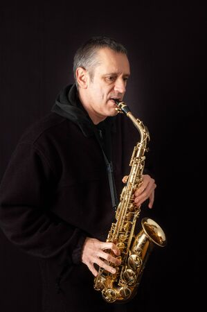 A Musician playing jazz music on his saxophone, on black background
