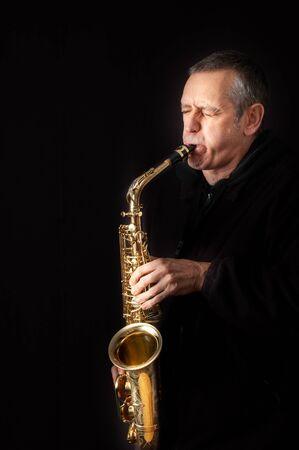 Un musicien jouant de la musique jazz sur son saxophone, sur fond noir