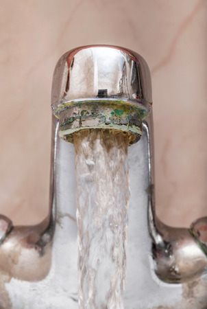 Vertical macro image of a tap with water flowing strongly under high pressure