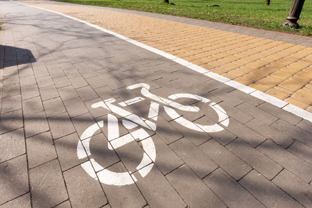 White bike path sign painted on a lane in the Natalka park of Kiev, Ukraine Фото со стока
