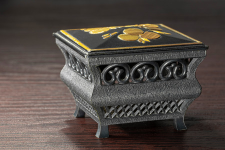 Little black and gold jewel case on a dark wooden table