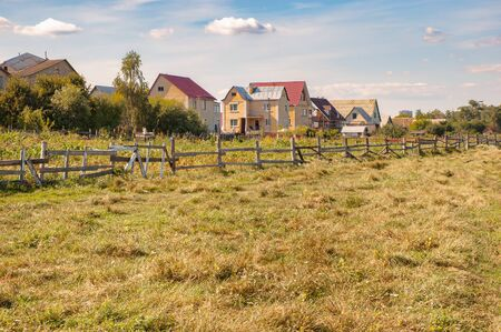Some houses of the small town of Irpin, northwest of Kiev in Ukraine, seen from the surrounding fields. In the foreground we can see the green grass and a wooden fence