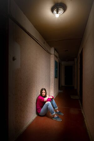 A sad and desperate woman sits in a dark corridor illuminated by a gloomy light. Her pain and her many problems pushed her into complete isolation. His sadness is only equalled by his loneliness.