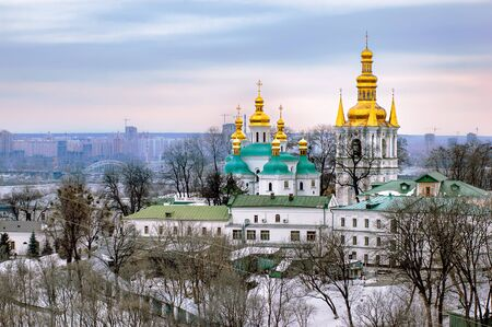 A view of the Lavra Monastery in Kiev with golden steeples. The town appears in background, under a cloudy winter sky