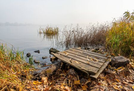 A wooden pontoon over big stones close to the blue Dnieper river is waiting for the fisherman.