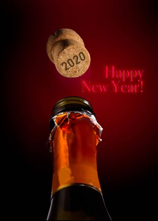 Bottle of Champagne and popping cork with  2020 written on it for new year two thousand eighteen