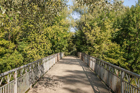 A bridge through the trees in the Ukrainian country side, during summer Archivio Fotografico