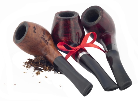 sherlock: Three wooden pipes with scattered tobacco and with a red ribbon. Stock Photo