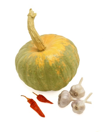 A still-life. Pumpkin, sheaf of garlic and hot red pepper. Stock Photo