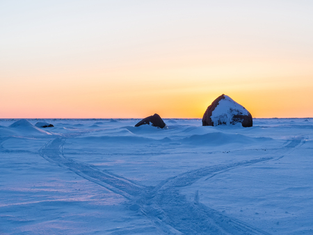 Beautiful winter landscape. Sunset in ices. Track in snow. Baltic Sea. Gulf of Finland. Russia.