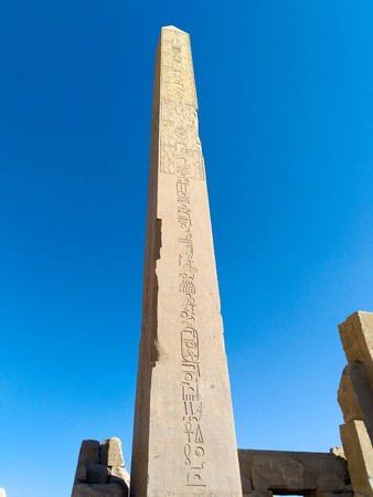 Ruins of an ancient temple of Egypt with statues and columns. Obelisk view