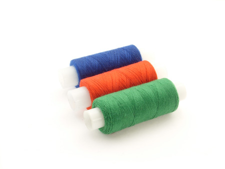 silk wool: three spools of thread on white background