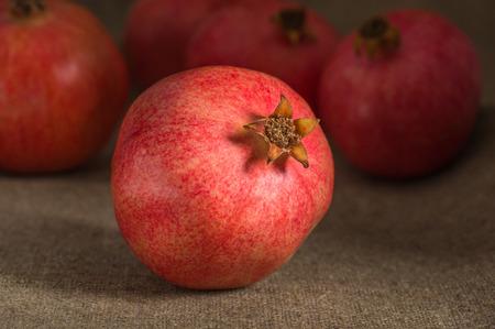 pomegranate on sackcloth background on the garnet group Stock Photo
