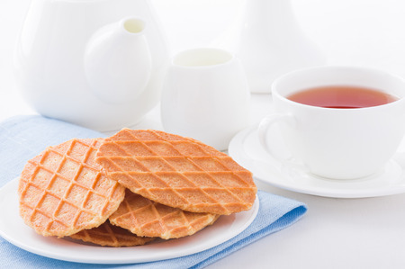 Sweet waffles on white plate, cup, milk jug and teapot background Stock Photo
