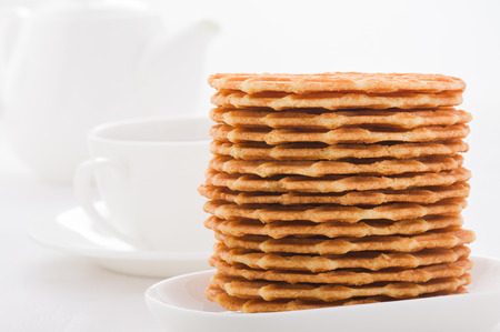 Sweet waffles on white plate, cup and teapot background