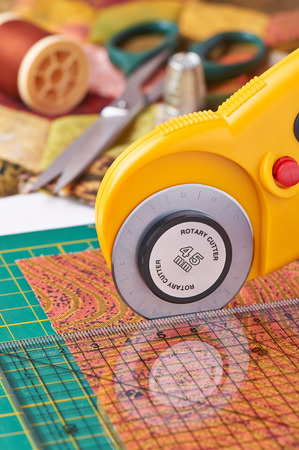 Rotary cutter cuts fabric on the a with a ruler Stock Photo