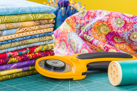 Rotary cutter and spool of thread on a background fabric Stockfoto