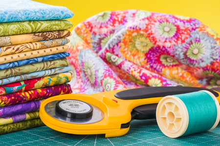 Rotary cutter and spool of thread on a background fabric Stock Photo