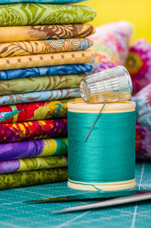 thread: Spool of thread with needle and thimble on the background