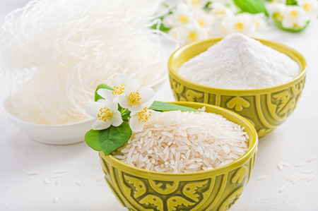 Bowls of rice and rice flour and jasmine flower