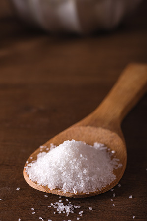 Sea salt in a bamboo spoon on wooden table Stock Photo