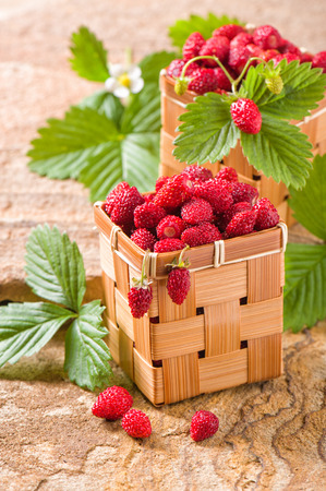 Strawberries in a basket on a stone Stock Photo