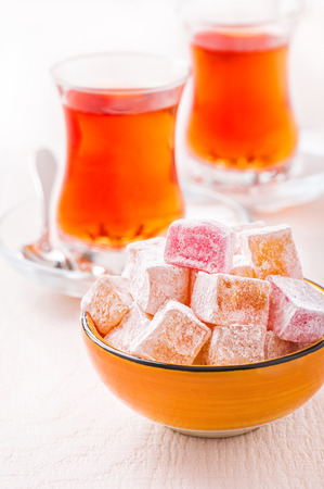 Bowl with Turkish delight cubes against the background of two glasses of tea