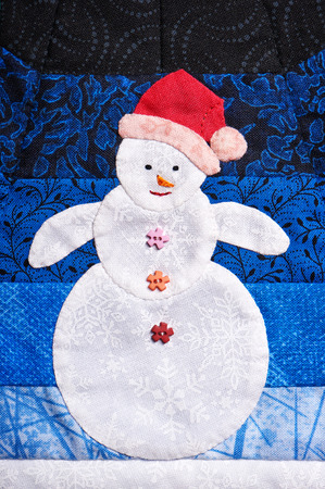 Patchwork snowman made out of pieces of fabric with texture of snowflakes