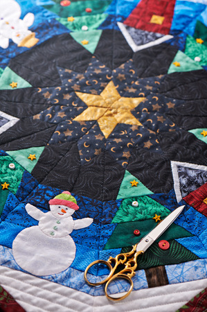 Detail of a Christmas quilt with scissors Stock Photo