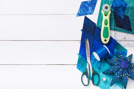 Accessoires voor patchwork top uitzicht op een witte houten oppervlak Stockfoto