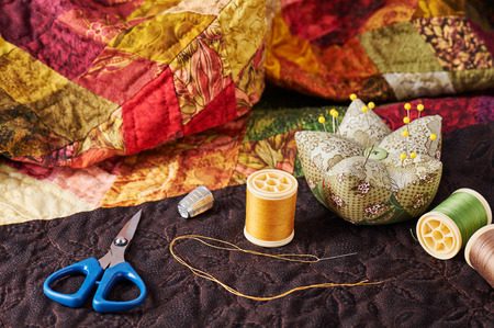 Spools of thread, needle, thimble, scissors and pin cushion for patchwork on a quilt
