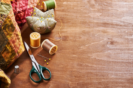 patchwork quilt: Spools of threads, needle, thimble, scissors and pin cushion on a wood background