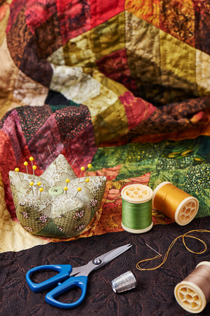 patchwork quilt: Spools of thread, needle, thimble, scissors and pin cushion for patchwork on a quilt