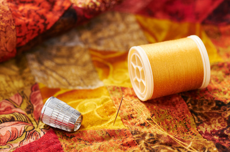 Spool of thread, needle and thimble on a quilt