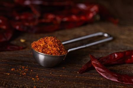 Measuring spoon with ground pepper on a wooden surface Stock Photo