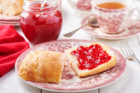 Strawberry jam spread on a slice of bread lying on a plate