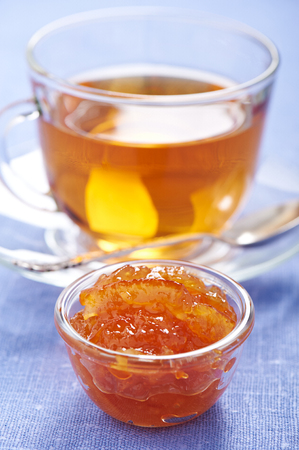 Orange jam in little bowl and cup of tea on background Stock Photo