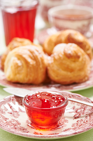 Quince-cranberry jelly in little glass bowl for breakfast on background croissants Stock Photo