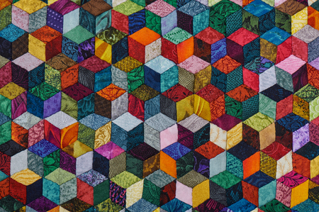 Colorful detail of quilt sewn from diamond pieces has view like three-dimensional